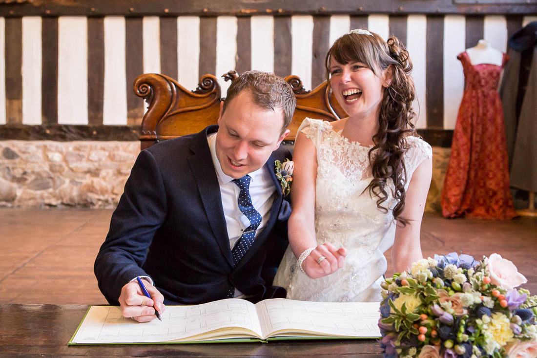 Leicestershire wedding photographer: James and Nicola sign the register at Leicester Guildhall