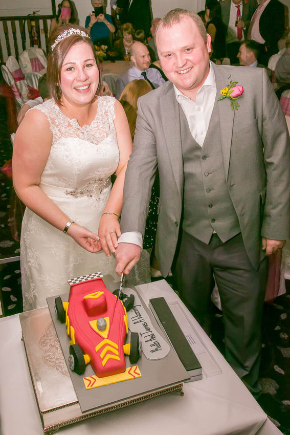 Leicestershire wedding photographer: James and Ruth cut the racing car cake