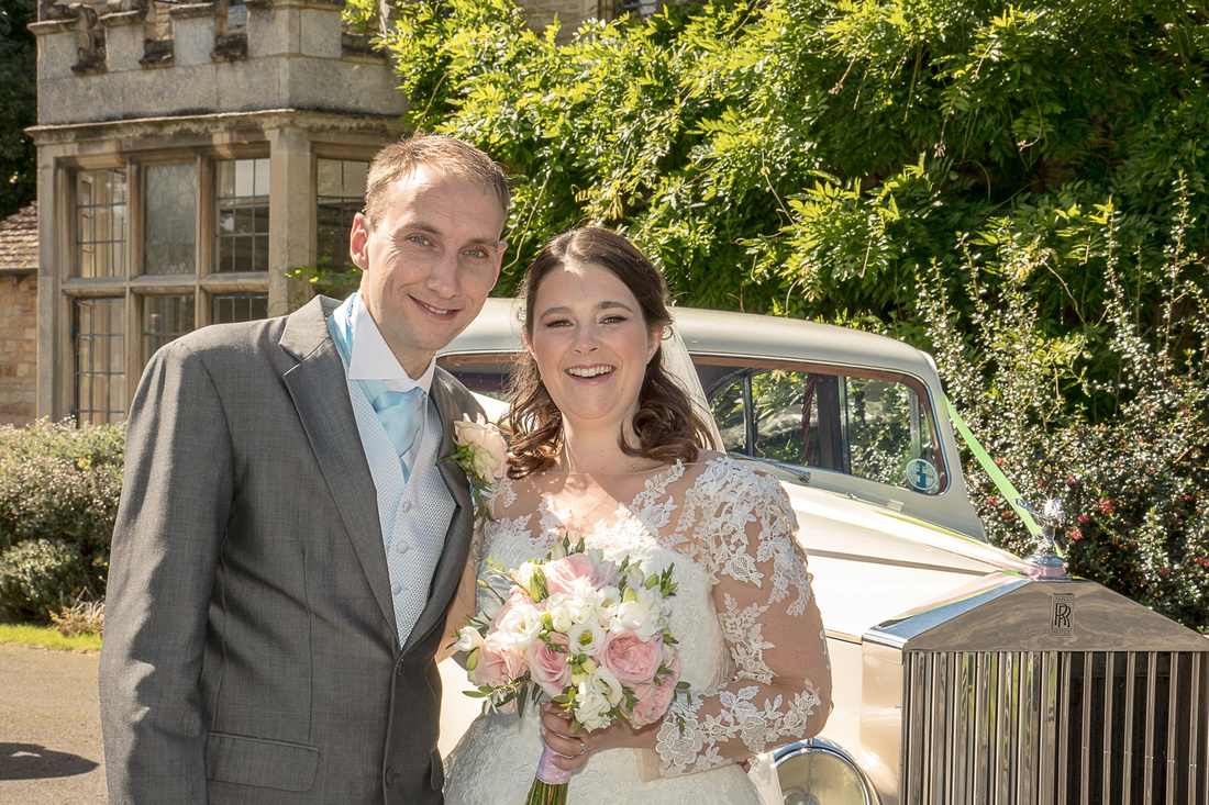 Wedding photography: Michael and Charlotte with wedding car at Rushden Hall Park
